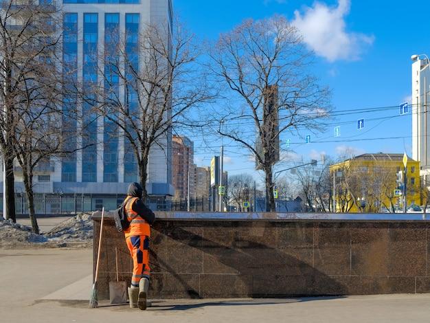 Een nutswerker in een oranje uniform rust op een granieten borstwering op een straat in de stad op een zonnige lentedag. er is een bezem en een schep in de buurt.
