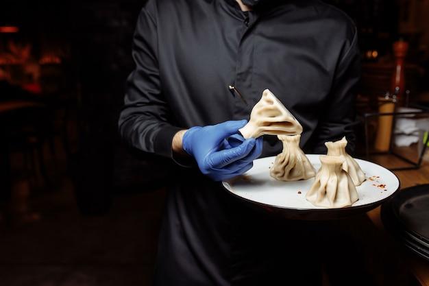 Een ober in een handschoen houdt een khinkali in zijn hand.