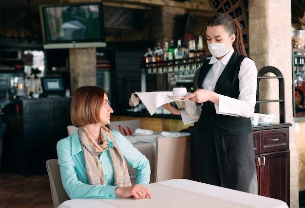 Een ober in europese stijl met een medisch masker serveert koffie.