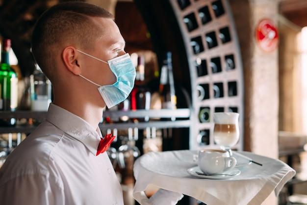 Een ober in europese stijl met een medisch masker serveert latte-koffie.