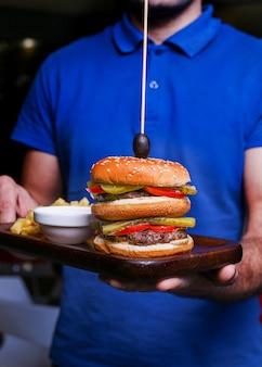 Een ober met een bord fastfood met hamburger en gebakken aardappelen.