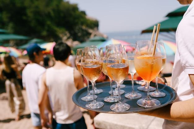 Een ober met een dienblad in de hand draagt cocktails en drankjes op een feestje op het strand een sinaasappelcocktail