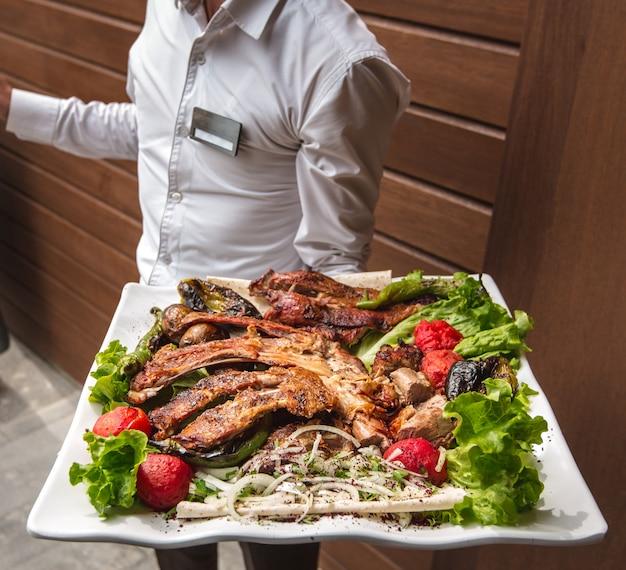 Een ober met een groot bord kebab kip in zijn hand