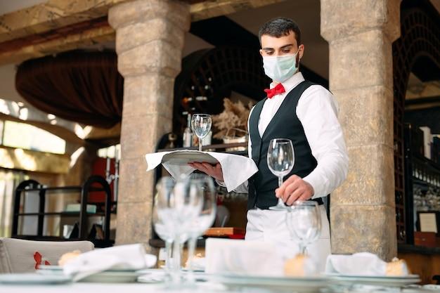 Een ober met een medisch beschermend masker bedient de tafel in het restaurant.