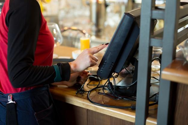Een ober van een modern café of bar voert een bestelling of betaling in via een tablet of een seekipper.