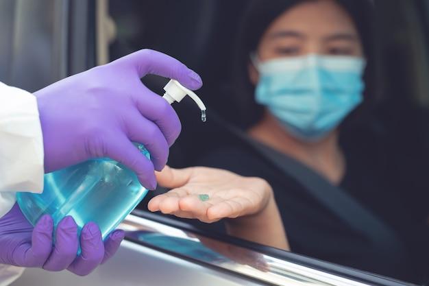 Een officier knijpt handdesinfecterend middel op een vrouw in een zwart shirt die in een auto zit.