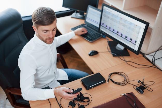 Een ogenblikje en we zijn klaar. polygraaf-examinator werkt op kantoor met de apparatuur van zijn leugendetector