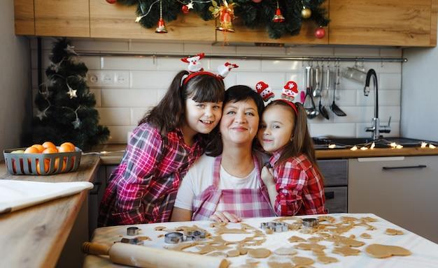 Een oma en twee kleindochters omhelzen elkaar in de keuken aan de vooravond van kerst. alledaagse levensstijl in het interieur van het echte leven.