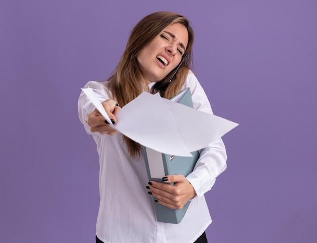 Een onaangenaam jong, vrij blank meisje steekt vellen papier uit om de bestandsmap te bewaren en aan de telefoon te praten