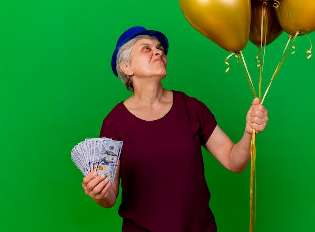 Een onaangename bejaarde vrouw die een feestmuts draagt, houdt geld vast en kijkt naar heliumballonnen op groen