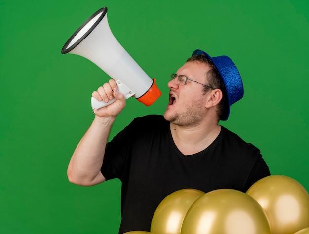 Een onaangename volwassen slavische man met een optische bril met een blauwe feestmuts houdt heliumballonnen vast en schreeuwt in een luidspreker die naar de zijkant kijkt