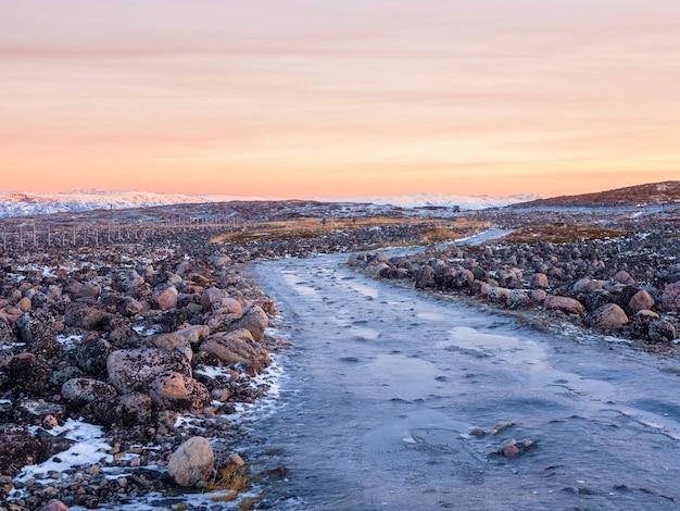 Een onbegaanbare ijzige weg door de winterse toendra. een ruwe, rotsachtige weg die zich uitstrekt in de verte. kola-schiereiland.