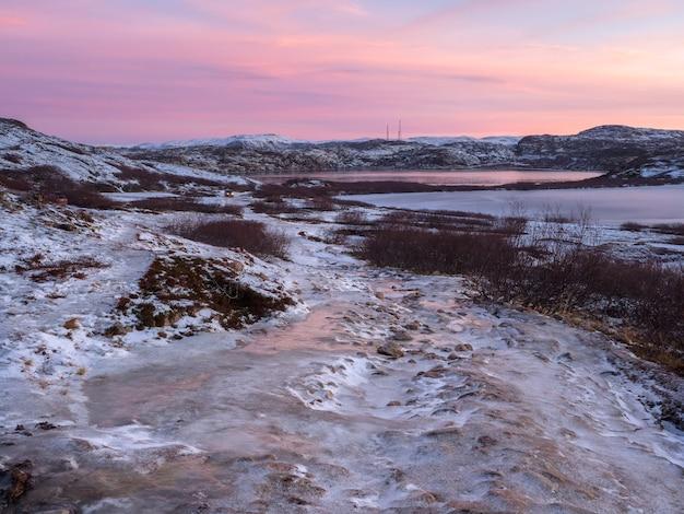 Een onbegaanbare ijzige weg door de wintertoendra. een ruwe, rotsachtige weg die zich in de verte uitstrekt. kola-schiereiland.