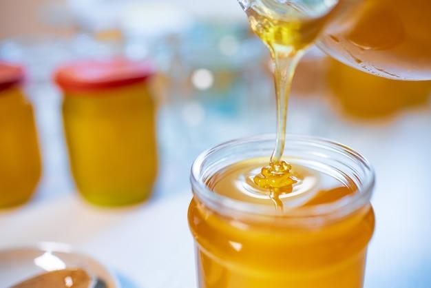 Een onbekende persoon giet zoete gouden honing in transparante lege schone potten die op een zonnige dag op een houten witte grote tafel staan