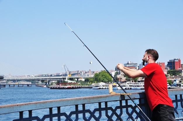 Een onbekende visser vangt vis vanaf de brug. een man vist in istanbul vanaf de galatabrug. vissen. 10 juli 2021 istanbul, turkije