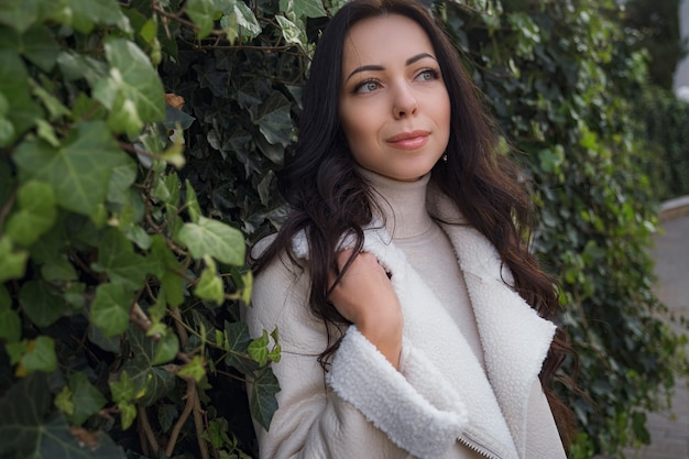 Een onbezorgde blanke vrouw in beige kleding die geniet van de warme, winderige dag