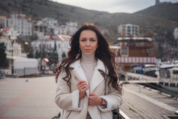 Een onbezorgde blanke vrouw in beige kleding die op een warme, winderige dag geniet van het uitzicht op zee