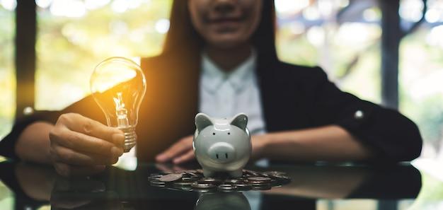 Een onderneemster die een gloeilamp naast een spaarvarken op stapel van muntstukken op de lijst voor geldbesparingsconcept houdt