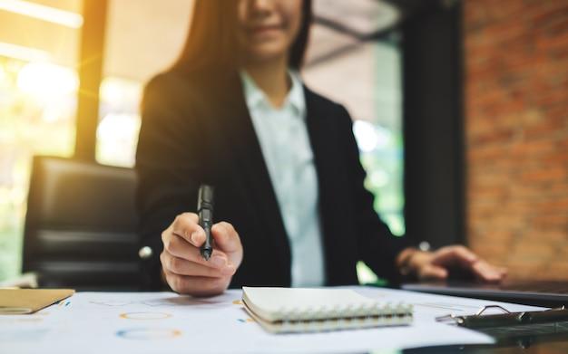 Een onderneemster die en aan bedrijfs financiële gegevens en laptop computer op de lijst in bureau schrijft werkt