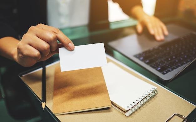 Een onderneemster die en een leeg adreskaartje houdt geeft terwijl het werken aan laptop computer en administratie op de lijst in bureau