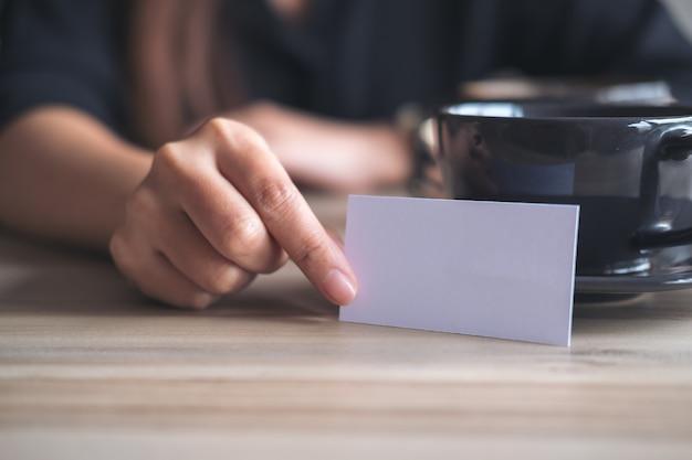 Een onderneemster die en een leeg adreskaartje voor een koffiekop houdt toont