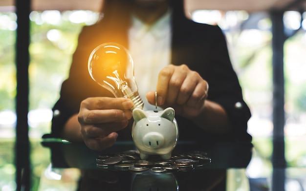 Een onderneemster die muntstukken en een gloeilamp over spaarvarken voor het concept van het besparingsgeld zet