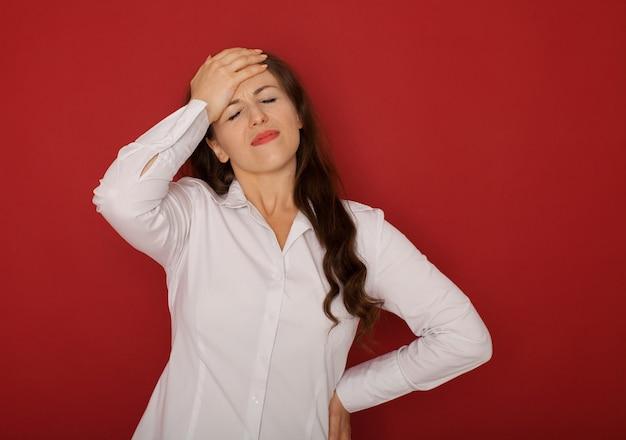 Een onderneemster met het hoofd van de hoofdpijnholding, dat op rood wordt geïsoleerd