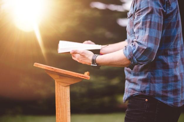 Een ondiepe focus shot van een man die de bijbel leest terwijl hij in de buurt van een podium staat
