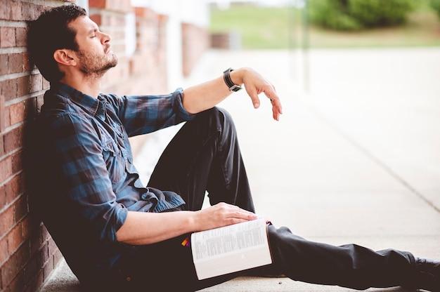 Een ondiepe focusopname van een man die op de grond zit terwijl hij bidt