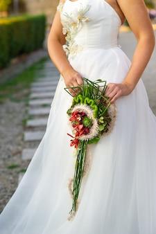 Een ongebruikelijk langwerpig bruidsboeket in de handen van de bruid.