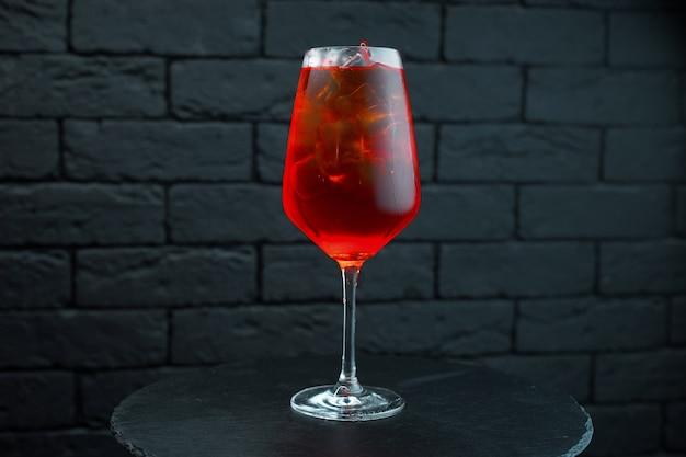 Een ongebruikelijke zoete lekkere rode cocktail in een glasglas met wodka met natuurlijk sap met toevoeging van granaatappelsiroop en witte rum staat op tafel in de bar. de drank wordt gekoeld geserveerd.
