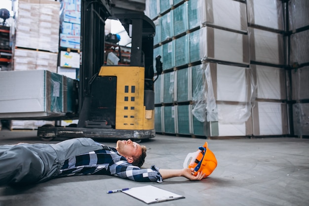 Een ongeluk in een magazijn, man op de vloer