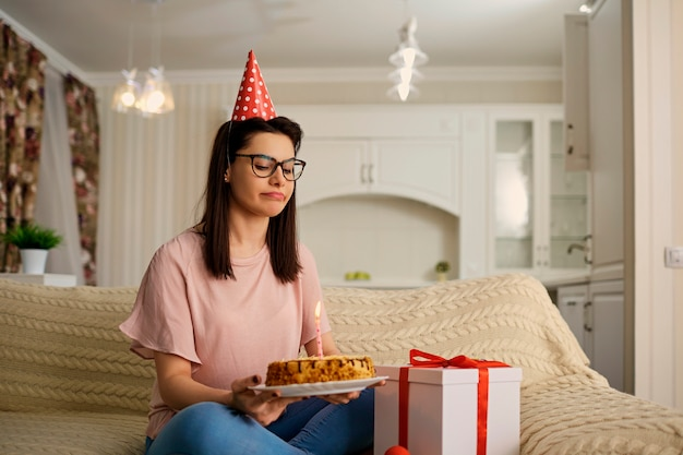 Een ongelukkig meisje met een hoed op haar verjaardag met een taart met kaarsen is alleen in de kamer.