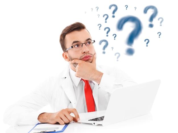 Een ongelukkige arts met laptop en documenten die op kantoor zitten