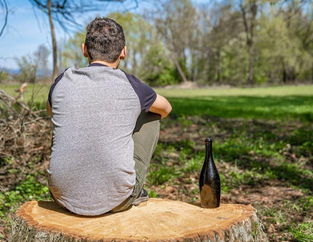 Een ongelukkige man lost problemen met alcohol op. verdrietig en alleen met een fles alcohol in de natuur