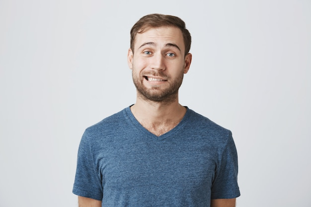 Een ongemakkelijke glimlachende man voelt zich besluiteloos