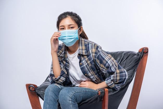 Een ongemakkelijke vrouw die op een stoel zit en een masker draagt
