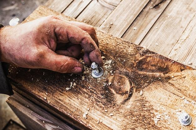 Een ongepolijste houten plank ligt op de grond, mannenhanden schroeven er een metalen bout in