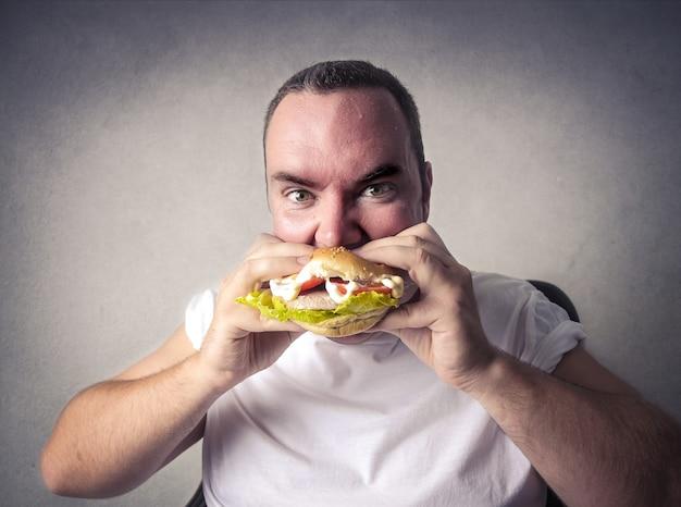 Een ongezonde hamburger eten