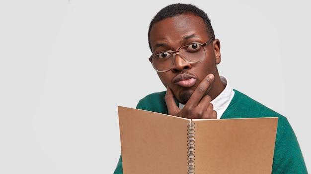 Een onhandige, bedachtzame zwarte mannelijke auteur draagt een bril met dikke lenzen, houdt de kin vast en kijkt verbijsterd