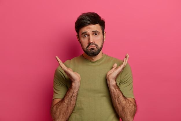 Een onhandige, onwetende man spreidt aarzelend zijn handpalmen