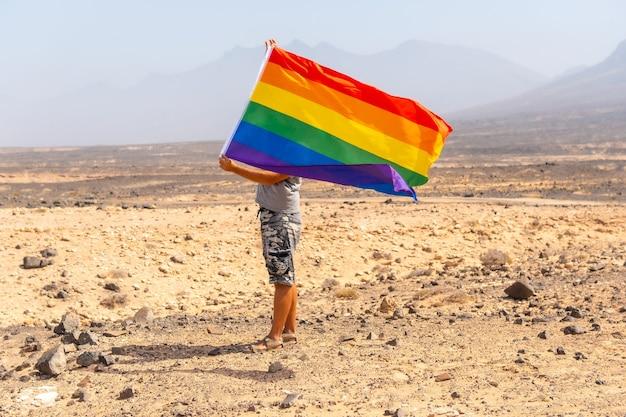 Een onherkenbare homo in een grijs t-shirt en zwarte pet met de lgbt-vlag zwaaiend in een woestijn met de wind, een symbool van homoseksualiteit