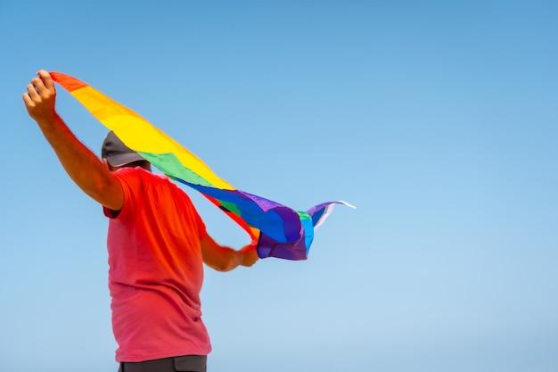 Een onherkenbare homo in een roze t-shirt met de lgbt-vlag die met de wind in een woestijn beweegt, symbool van homoseksualiteit