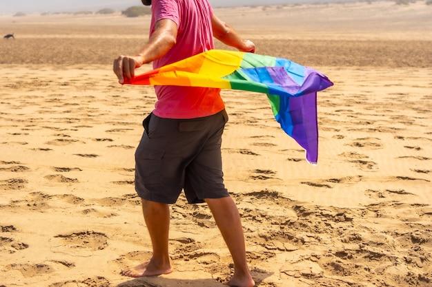 Een onherkenbare homo met de lgbt-vlag waait in de wind in een woestijn, symbool van homoseksualiteit, regenboogvlag