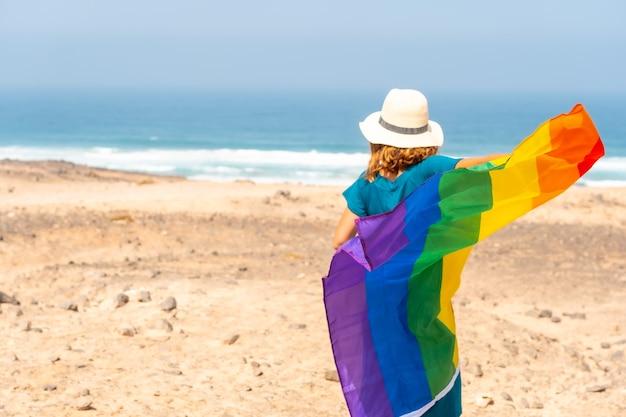 Een onherkenbare lesbische persoon in een groene jurk en met de lgbt-vlag bij de zee, symbool van homoseksualiteit