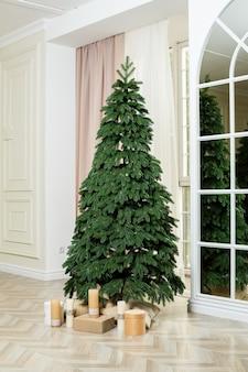 Een onopgesmukte kerstboom met cadeautjes eronder. goede nieuwjaarsgeest.