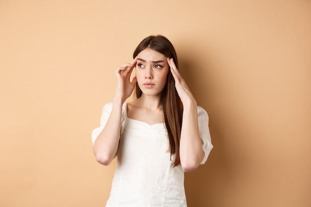 Een onrustige jonge vrouw voelt zich misselijk, raakt de slapen van het hoofd aan, heeft hoofdpijn, kijkt naar de linkerbovenhoek met een gespannen en verontrust gezicht, staande op een beige achtergrond.