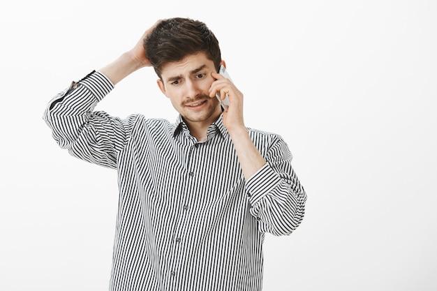 Een onrustige officemanager kan geen antwoord geven. portret van verwarde ondervraagde knappe mannelijke student met snor, achterhoofd krabben en praten over smartphone, naar beneden te kijken, excuses maken