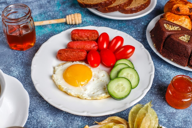 Een ontbijtbord met cocktailworstjes, gebakken eieren, cherrytomaatjes, snoep, fruit en een glas perziksap.