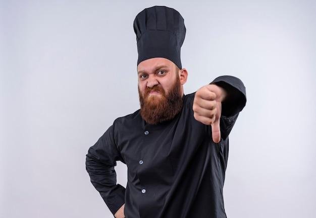 Een ontevreden, bebaarde chef-kok in zwart uniform met duimen naar beneden terwijl hij op een witte muur kijkt